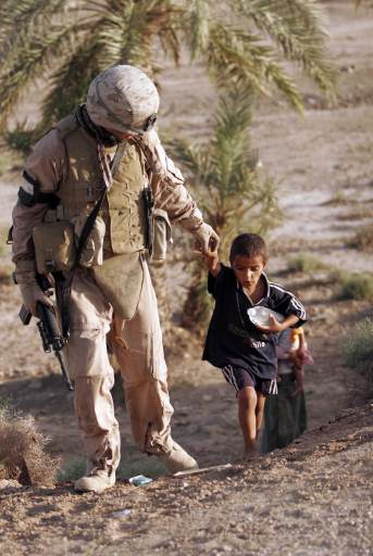 soldier walks with a child in Iraq