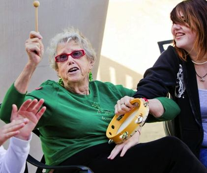 elderly woman plays tamborine - EngAGE photo