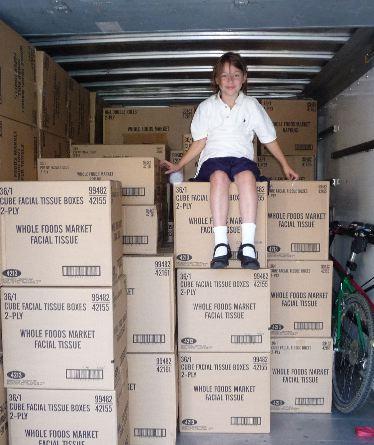 schoolgirl-atop-cartons-green-products.jpg