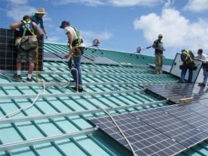 students work on a roof with solar panels