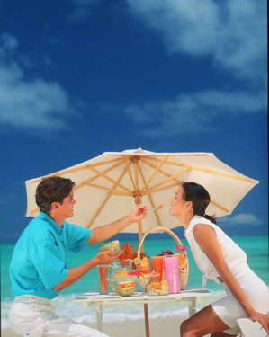 couple-under-beach-umbrella-eating-sunstar