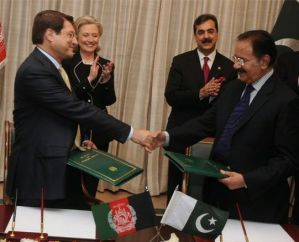 Pakistan and Afghan trade reps signing as Hillary looks on