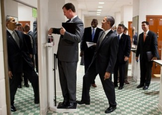 """We were walking through a locker room at the University of Texas when White House Trip Director Marvin Nicholson stopped to weigh himself on a scale. Unbeknownst to him, the President was stepping on the back of the scale, as Marvin continued to slide the scale lever. Everyone but Marvin was in on the joke."" (Official White House Photo by Pete Souza)"