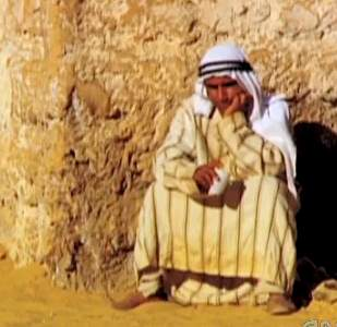 Arab man leans against wall