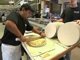 pizza maker cuts pie at Nick's
