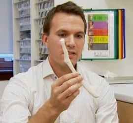 Doctor holds plastic bone - BBC video snapshot