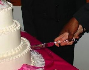 interracial couple cuts wedding cake by kakisky, via Morguefile