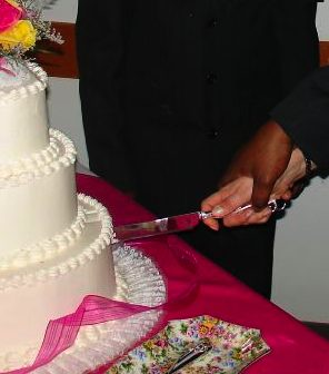interracial couple cuts wedding cake by kakisky, via Morguefile