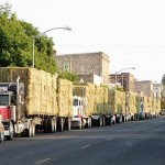 trucks with hay line US street by Stephanie Falck