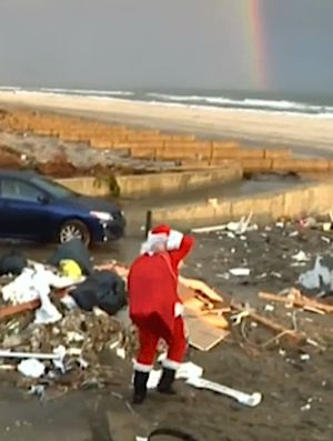 Santa on storm-ravaged beach with rainbow - AP video snippet