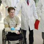 wheelchair amputee with doctors - Johns Hopkins photo by Keith Weller