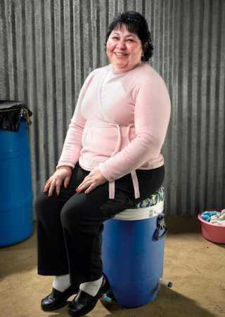 Peruvian woman seated on the laundry machine