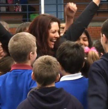 woman cheers amid schoolkids (video screenshot)