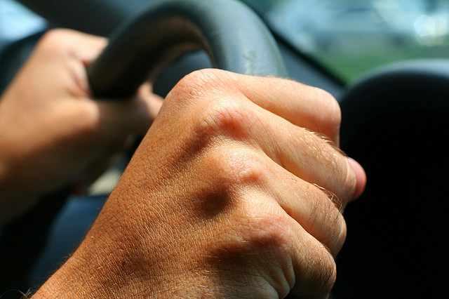 mans-hand-on-steering-wheel-grip-nate steiner-flickr-cc