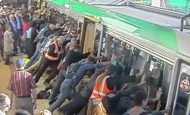 commuters use people power to push train off trapped man