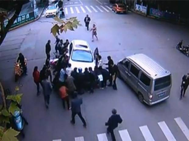 Crowd in China lifts car off woman-surveillence-camera following crash