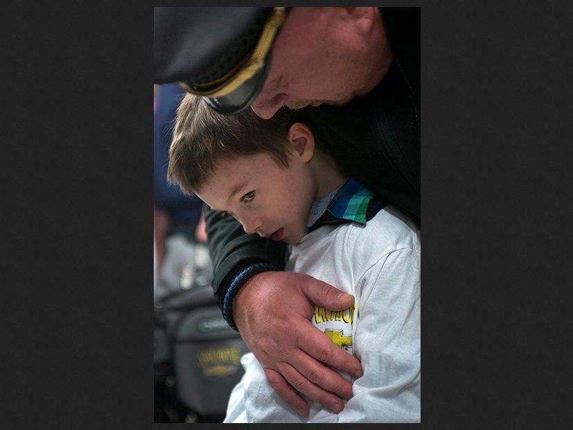 Brimfield Township Police Chief David Oliver comforts 6yo Kashe Heffelfinger
