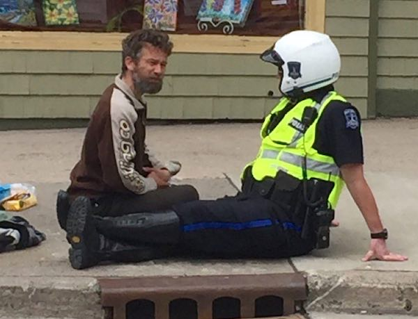 cop sits on street with homeless man-Bruno Baurin-Twitter