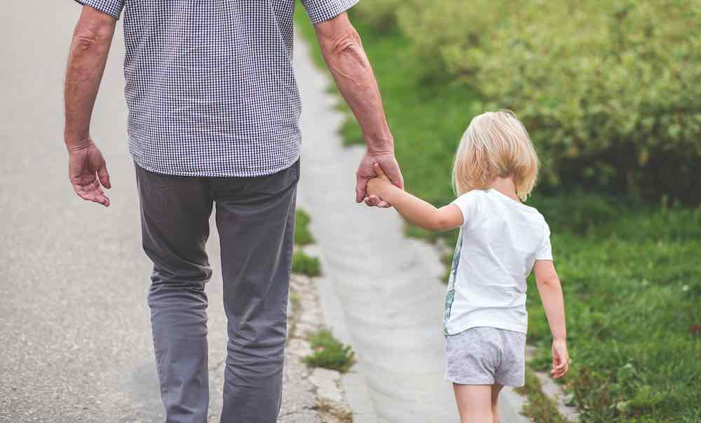 Senior-Holding-Hands-With-Young-Child%E2